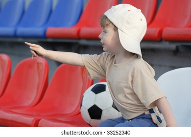 The young fan on a tribune of stadium observes of game in football