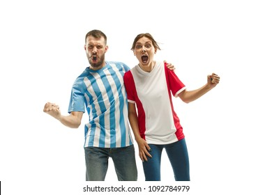 The young fans celebrating on white background. The young man in soccer football uniform and girl as winner isolated at white studio. Fan, support concept. Human emotions concept.