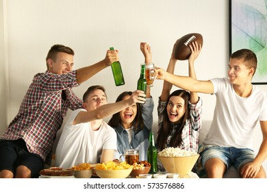 Young fans watching rugby match on TV with beer and snacks