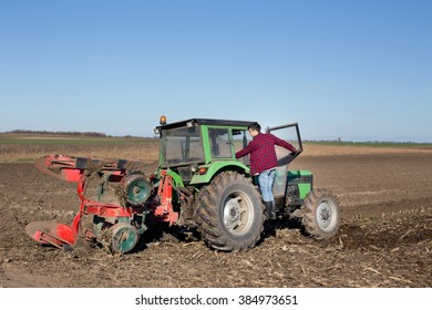 Young farmer climbing on tractor in the field