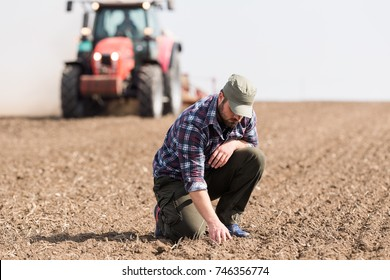Young farmer is examing dirt while tractor is plowing field