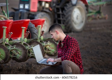 Young farmer with laptop squatting in field in front of tractor with sowing equipment. Smart technology in agriculture