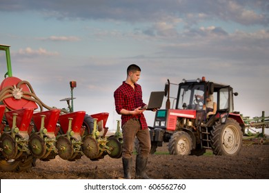 Young farmer with laptop standing in field in front of tractor with smart sowing equipment