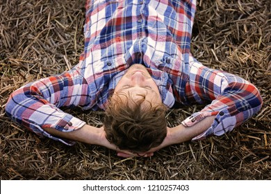 A young farmer man in a flannel shirt is taking a break and relaxing on a hay bale on an Autumn day.