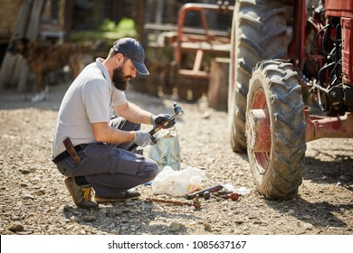 Young farmer repairing his tractor in a sunny day