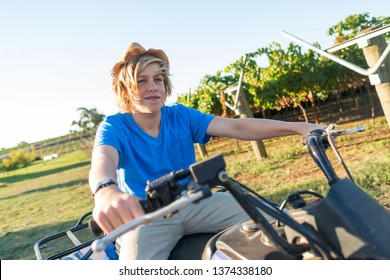 Young farmer riding quad bike on background of vine rows. Traditional farming in vineyard. Happy blond guy in straw hat and and blue t-shirt sitting on bike. Ecological food production in countryside.
