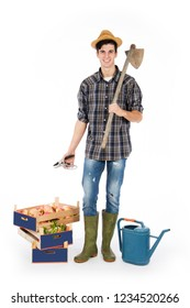 Young farmer with shears in his hand and hoe on his shoulder, at his feet crates with fruit and vegetables, he is wearing a straw hat, checked shirt and green rubber boots