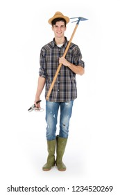 Young farmer with shears and hoe in hands, he is wearing a straw hat, checked shirt and green rubber boots