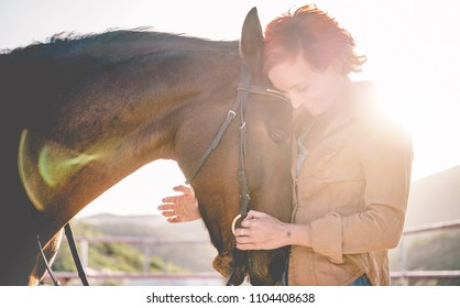 Young farmer woman hugging her horse - Concept about love between people and animals - Focus on pet face
