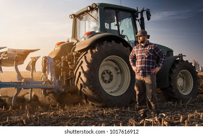 Young farmer working during the tractor plowing fields -preparing land for sowing