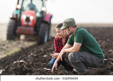 Young farmers examing dirt while tractor is plowing field