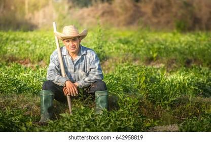 Young farmers sit in potato garden.