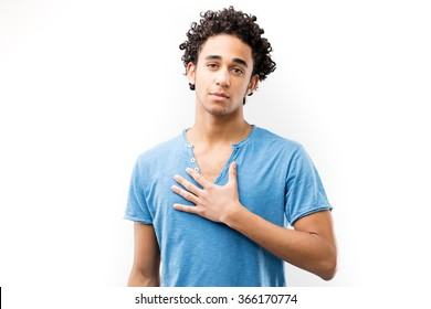 young fascinating man with his hand on his chest meaning he's dedicated and his deep feelings come from his heart