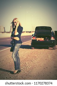 Young fashion blond business woman calling on cell phone next to broken car Stylish female model wearing dark blue blazer and jeans outdoors