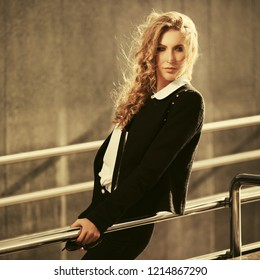 Young fashion blond business woman leaning on railing Stylish female model wearing black jacket and white shirt