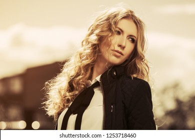 Young fashion blond business woman walking on city street Stylish female model wearing black jacket and necktie