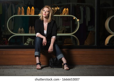 Young fashion blond business woman sitting on the mall window Stylish female model in black blazer