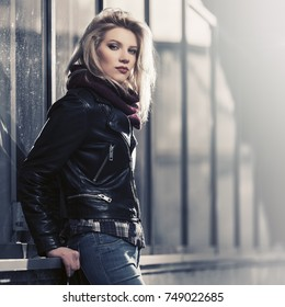 Young fashion blond woman at the mall window Stylish female model in black leather jacket outdoor