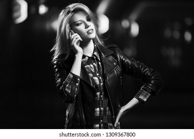 Young fashion blond woman talking on cell phone on city street at night Stylish female model wearing black leather jacket