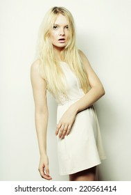 young fashion blond woman in white dress posing in studio