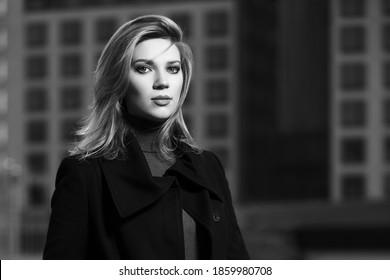 Junge Mode-blonde Geschäftsfrau geht auf der Straße Stylische Frauenmodell in klassischem schwarzen Mantel