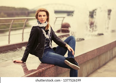 Young fashion blonde woman sitting on parapet Stylish trendy model wearing black leather jacket and blue jeans