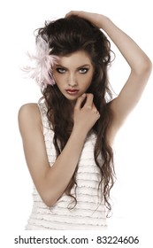 young fashion brunette posing on white wearing a pink feather in her hair