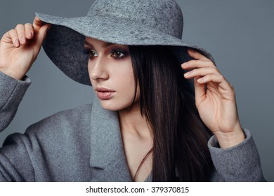 young fashion brunette woman beauty portrait posing in studio wearing in gray coat and hat