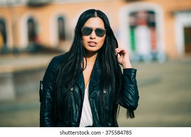 Young fashion brunette woman in sunglasses with jacket on city street. Series of poses.