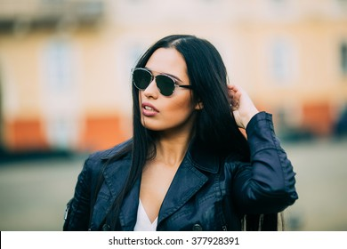 Young fashion brunette woman in sunglasses with jacket on city street