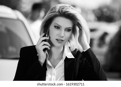 Young fashion business woman calling on cell phone on city street Stylish female model in black blazer and white shirt