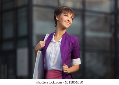 Young fashion business woman with handbag walking at the mall. Stylish female model wearing purple blazer and white shirt