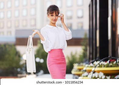 Young fashion business woman with handbag walking in city street Stylish female model wearing white blouse and pink pencil skirt outdoors
