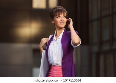 Young fashion business woman with handbag walking at the mall Stylish female model wearing purple blazer and white shirt