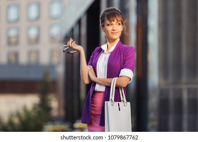 Young fashion business woman with handbag walking in city street Stylish female model wearing purple blazer and pink pencil skirt outdoors