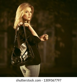 Young fashion business woman with handbag walking on city street Stylish female model with blond hair wearing black blazer and light blue jeans