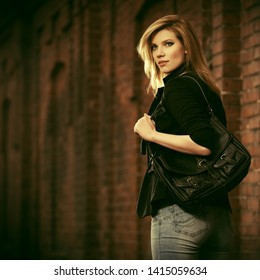 Young fashion business woman with handbag walking on city street Stylish female model with blond hair in black blazer and light blue jeans
