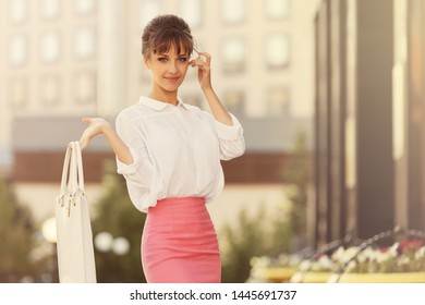 Young fashion business woman with handbag walking on city street Stylish female model in white shirt and pink pencil skirt