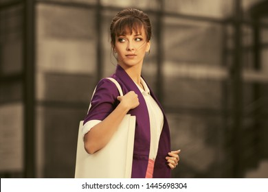 Young fashion business woman with handbag walking on city street Stylish female model in purple blazer with up do hair style