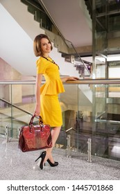 Young fashion business woman with handbag at office Stylish female model with bob hairstyle in yellow peplum dress