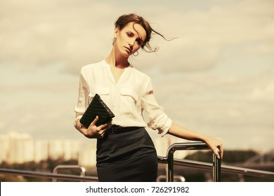 Young fashion business woman with handbag walking in a city street. Stylish female model in white blouse and pencil skirt outdoor