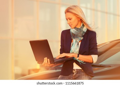 Young fashion business woman with laptop sitting on her car Stylish female model wearing dark blue jacket and turquoise scarf outdoor