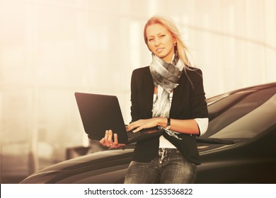 Young fashion business woman with laptop outside her car Stylish female model wearing black blazer and gray scarf outdoor