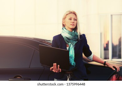 Young fashion business woman with laptop leaning on her car Stylish female model in dark blue blazer and green scarf