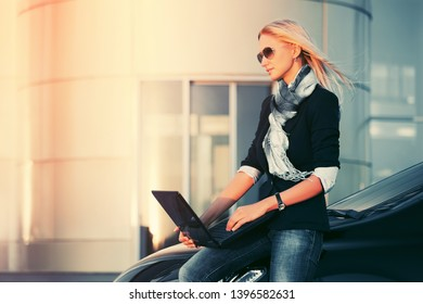 Young fashion business woman with laptop leaning on her car Stylish female model in dark blue blazer and gray scarf