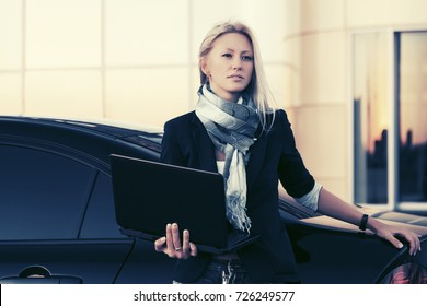 Young fashion business woman with laptop next to her car on parking. Stylish female model in black jacket and scarf outdoor