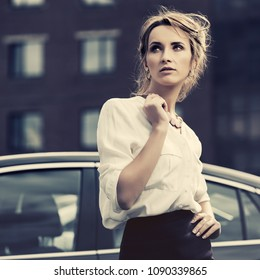 Young fashion business woman next to her car in city street Stylish female model with bun updo hair wearing white shirt and pencil skirt