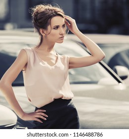 Young fashion business woman next to her car in city street Stylish female model with bun updo hair wearing pink sleeveless blouse and black skirt