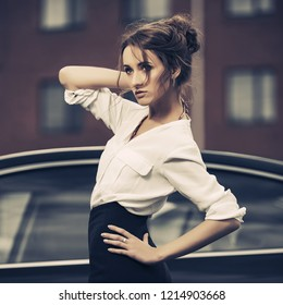 Young fashion business woman next to her car  Stylish female model with bun up do hair wearing white shirt and black pencil skirt