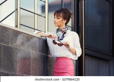 Young fashion business woman at office building Stylish female model in white shirt and pink pencil skirt outdoor